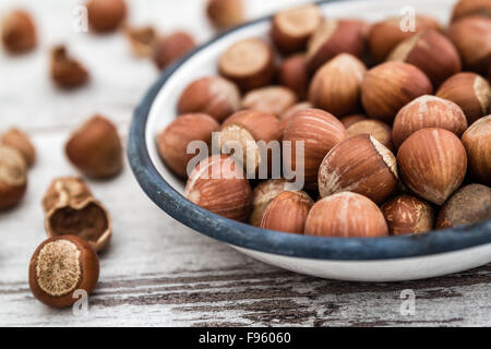 Hazelnuts in enamel bowl on white wooden table, top view - Stock Photo