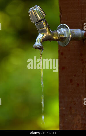 Water dripping from an outdoor tap in a recreation area on Vancouver Island British Columbia, Canada. - Stock Photo