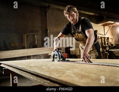 Carpenter cutting chipboard with a circular saw, Austria - Stock Photo