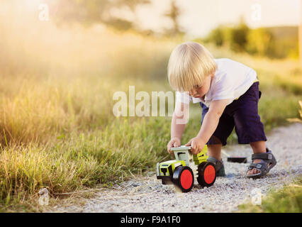 Little boy playing with toy tractor on countryside road - Stock Photo