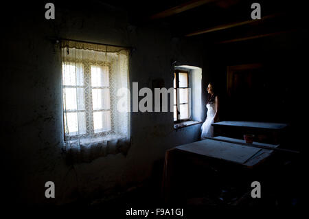Lovely and happy brunette bride posing in old house - Stock Photo