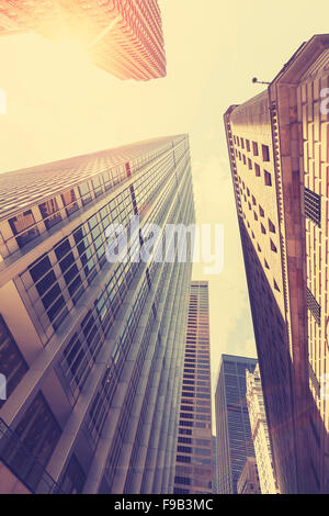 Retro stylized photo of skyscrapers in Manhattan at sunset with lens flare effect, New York City, USA. - Stock Photo