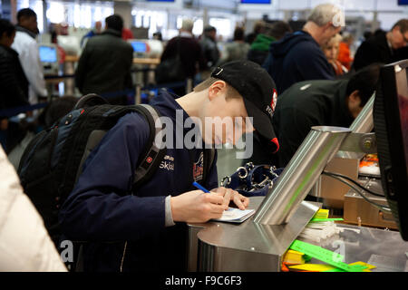 Young teen boy age 13 filling out forms at MSP International Airport Minneapolis Minnesota MN USA - Stock Photo
