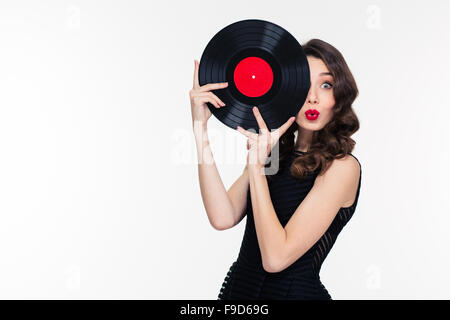 Playful beautiful charming curly woman with bright makeup in retro style covered half of face with vinyl disc - Stock Photo