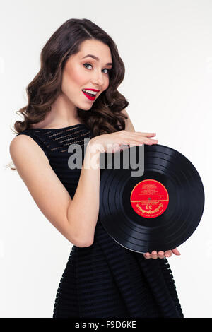 Portrait of attractive smiling retro styled young woman in black dress holding vinyl record over white background - Stock Photo