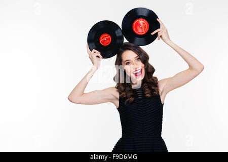 Funny cheerful curly young woman in retro style posing with vinyl records isolated over white background - Stock Photo