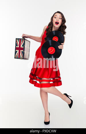 Full length of curly woman in retro style running on high heels with vintage suitcase and vinyl disks - Stock Photo