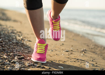 Young woman is running in sunny nature along the beach - Stock Photo