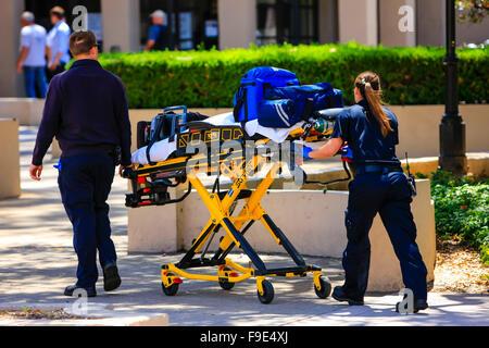 Paramedics pushing a gurny loaded with life saving equipment to a call out in downtown Santa Barbara, California - Stock Photo