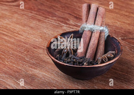traditional christmas spices - star anise, cloves and cinnamon bark sticks - on a wooden table - Stock Photo