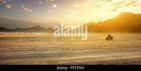 Sandy field in desert of Egypt at sunset - Stock Photo