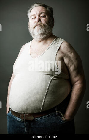 Portrait of senior man with full beard wearing vest - Stock Photo