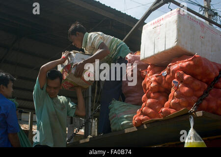 Two men are unloading a truck filled with vegetables at the main market in Ou Reang Ov District, Cambodia. - Stock Photo