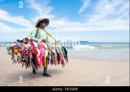 RIO DE JANEIRO, BRAZIL - MARCH 15, 2015: A beach vendor selling bikinis carries her merchandise along Ipanema Beach. - Stock Photo