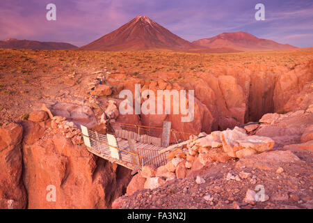 A rickety bridge over a narrow canyon with a volcano in the distance. Photographed at the foot of Volcan Licancabur - Stock Photo