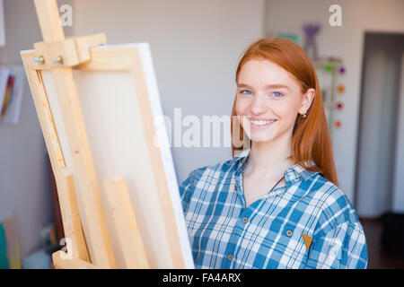 Pretty cheerful young woman painter in checkered shirt painting in art studio - Stock Photo