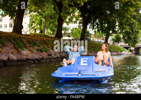 Friends enjoying pedal boating on river in city - Stock Photo