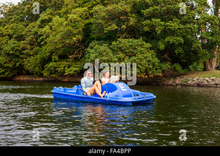 Man and woman enjoying pedal boating on river in city - Stock Photo