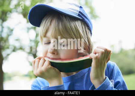 Boy enjoying slice of watermelon at picnic, Munich, Bavaria, Germany - Stock Photo