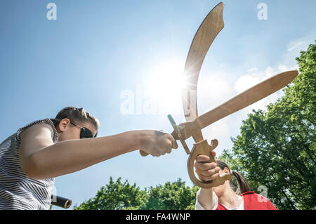 Low angle view of two girls pretending as pirates fighting with swords in adventure playground, Bavaria, Germany - Stock Photo
