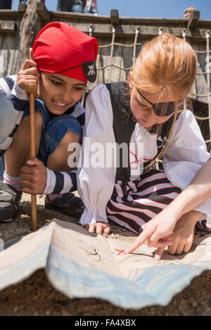 Two girls examining a treasure map in a adventure playground, Bavaria, Germany - Stock Photo