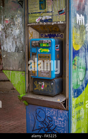 Vandalism and graffiti on a telephone in Buenos Aires, Argentina - Stock Photo