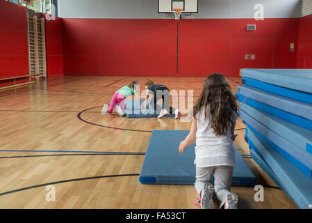 Girls arranging the sports mats in basketball court, Munich, Bavaria, Germany - Stock Photo