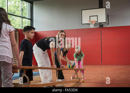 Teacher and students carrying bench in sports hall, Munich, Bavaria, Germany - Stock Photo