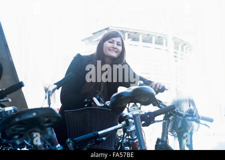 Young woman standing with bicycle in parking lot, Freiburg im Breisgau, Baden-Württemberg, Germany - Stock Photo
