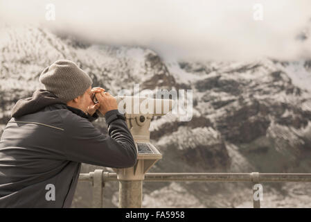 Mature man looking at mountain with telescope, Grossglockner mountain, National Park Hohe Tauern, Carinthia, Austria - Stock Photo