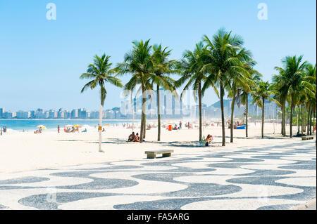 RIO DE JANEIRO, BRAZIL - NOVEMBER 10, 2015: Beachgoers take advantage of a bright afternoon on the Leme end of Copacabana - Stock Photo