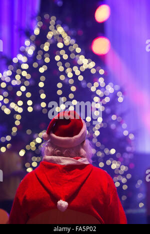 Berlin, Germany. 21st Dec, 2015. A man dressed as Santa Claus waits prior to a traditional Christmas party for homeless - Stock Photo