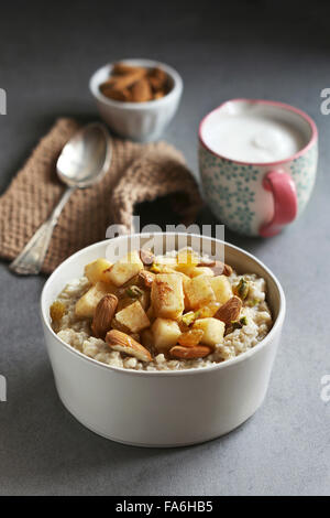 Oatmeal porridge in white ceramic bowl with apples,almonds and golden raisins - Stock Photo