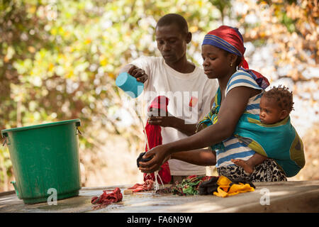 Community members wash their clothes with clean water in the village of Mecupes in Northern Mozambique. - Stock Photo
