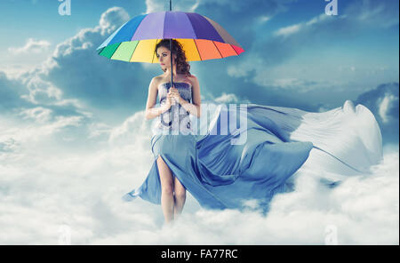 Brunette walking on the fluffy white clouds - Stock Photo