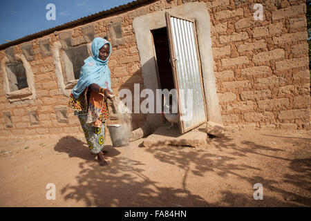 A farmer feeds her chickens outside her barn in Tengréla Village, Burkina Faso. - Stock Photo