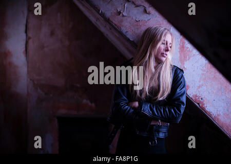 A sad lonely depressed young slim blonde haired woman alone in a rundown derelict room building UK - Stock Photo