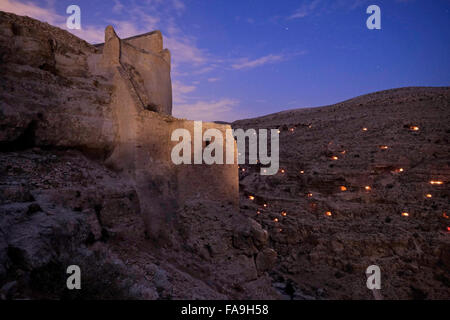 Light candles illuminating small caves near Mar Saba Monastery during Mar Saba Day in the Judaean or Judean desert - Stock Photo