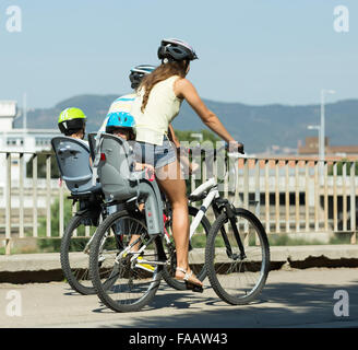 Young family with two little daughters traveling by bicycles - Stock Photo