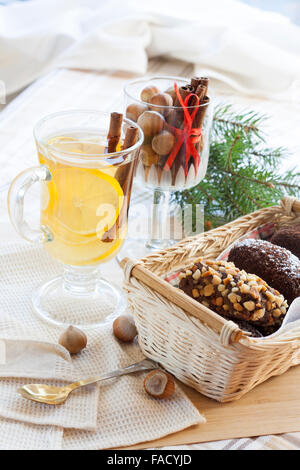 Fresh hot green tea in glass cup with lemon and cinnamon, chocolate cakes in basket and nuts and cinnamon in glass - Stock Photo