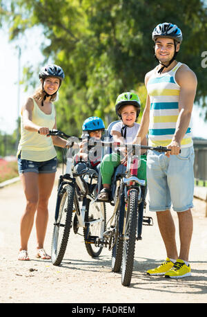 Family with two little daughters traveling by bicycles - Stock Photo