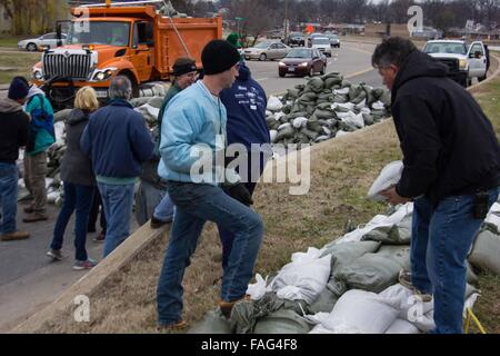 Missouri, USA. 29th Dec, 2015. Volunteers make an assembly line to pack sandbags on top of a river in St. Louis, - Stock Photo
