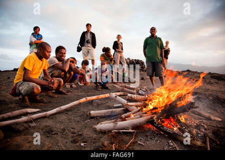 Tourists and local Nivans keep warm by a magma-started fire on Mt Yasur, an active volcano on Vanuatu's southern - Stock Photo