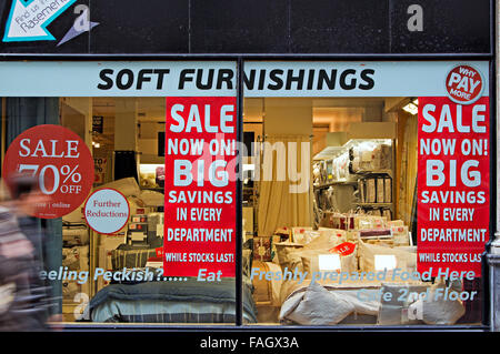 Big savings posters in a soft furnishing store window display - Stock Photo