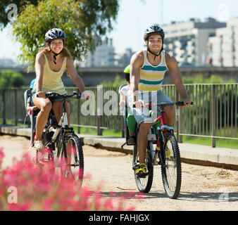 Happy young family with two little daughters traveling by bicycles. Focus on man - Stock Photo