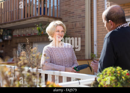 Happy elderly woman with horticultural sundry and aged man drinking tea in patio - Stock Photo
