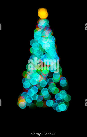 Abstract of fairy lights on an outdoor Christmas tree at night isolated on a black background - Stock Photo