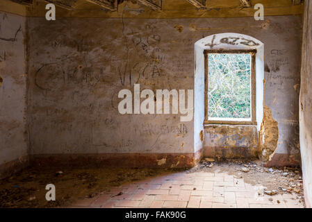 An abandoned room of an old collapsing farm house with the word 'Visca Catalunya' (long live Catalonia) scratched - Stock Photo