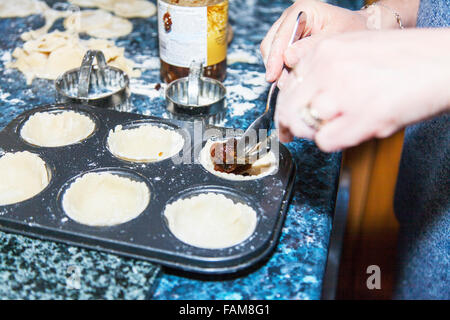 Making mince pies adding mincemeat to pastry cases cooking in kitchen baking tray - Stock Photo