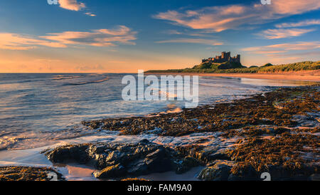 Bamburgh Castle at sunrise on the east cost of Northumberland, England. - Stock Photo